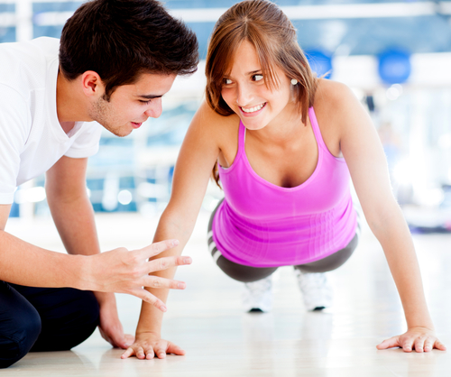 Personal trainer teaching exercise to woman