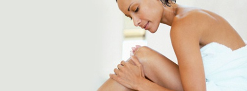 Woman applying skincare to legs