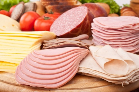 Assorted deli meat slices on wooden table