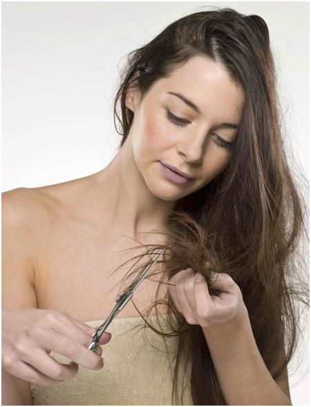 Woman trimming off her split ends