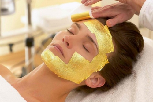 Woman enjoying gold facial at spa