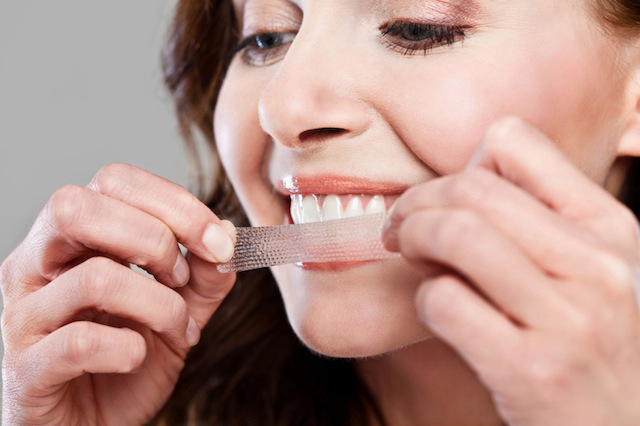 Woman using teeth whitening strips