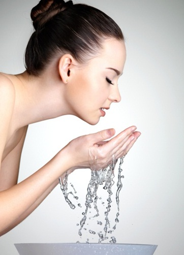 Woman rinsing face with water