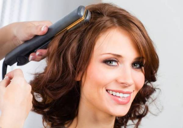 Woman having her done with heated hair straightener