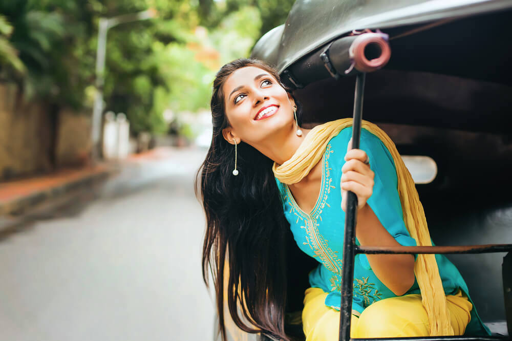 Happy single woman enjoying life from a rickshaw