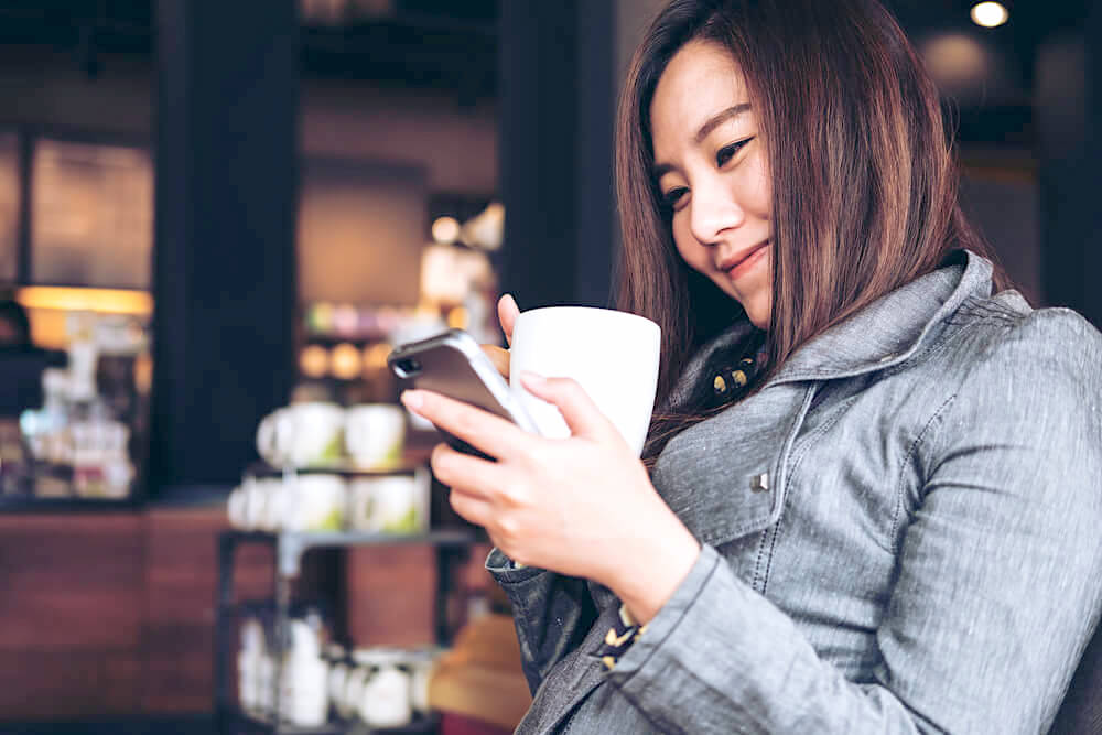 Smiling young woman texting on her phone while enjoying a cup of coffee