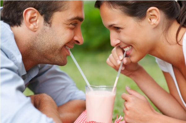 Couple using two straws to enjoy the same drink