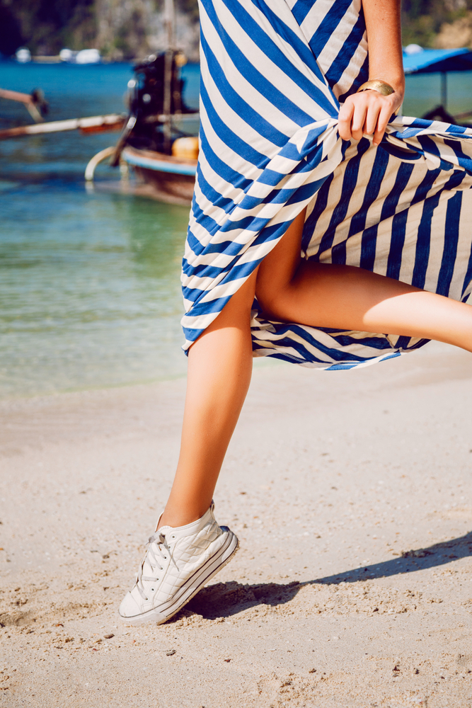 Woman's running legs in sneakers at the beach