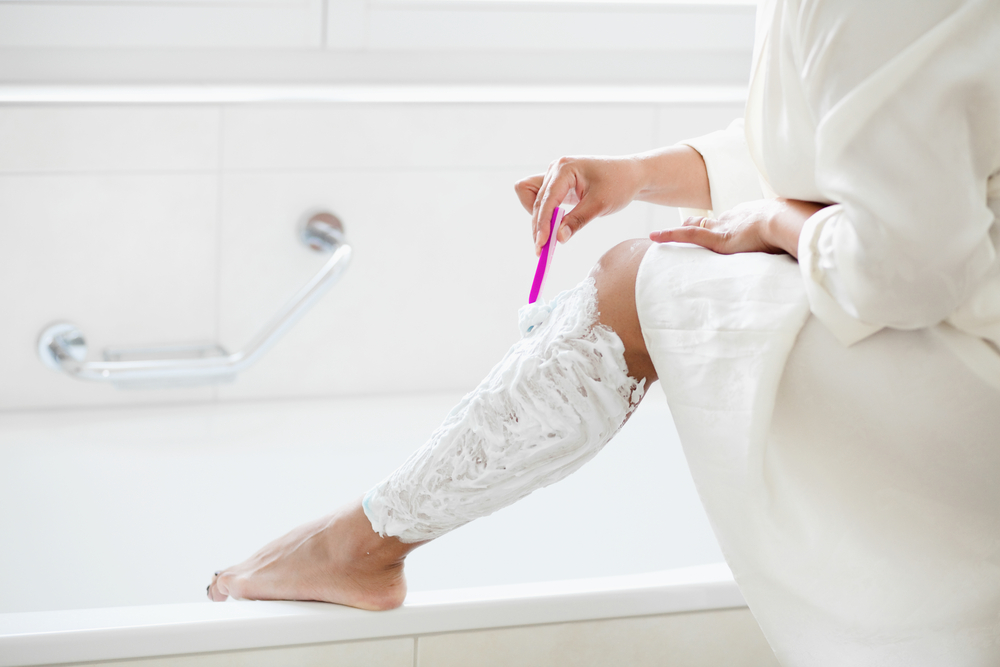Woman shaves her leg with shaving cream