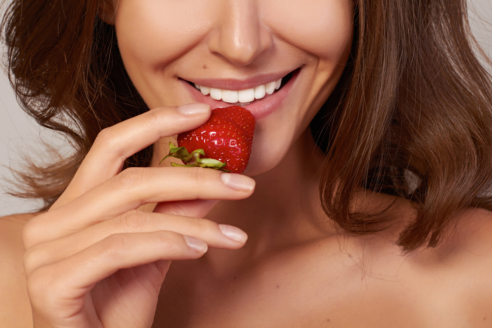 Woman with healthy nails eats a strawberry