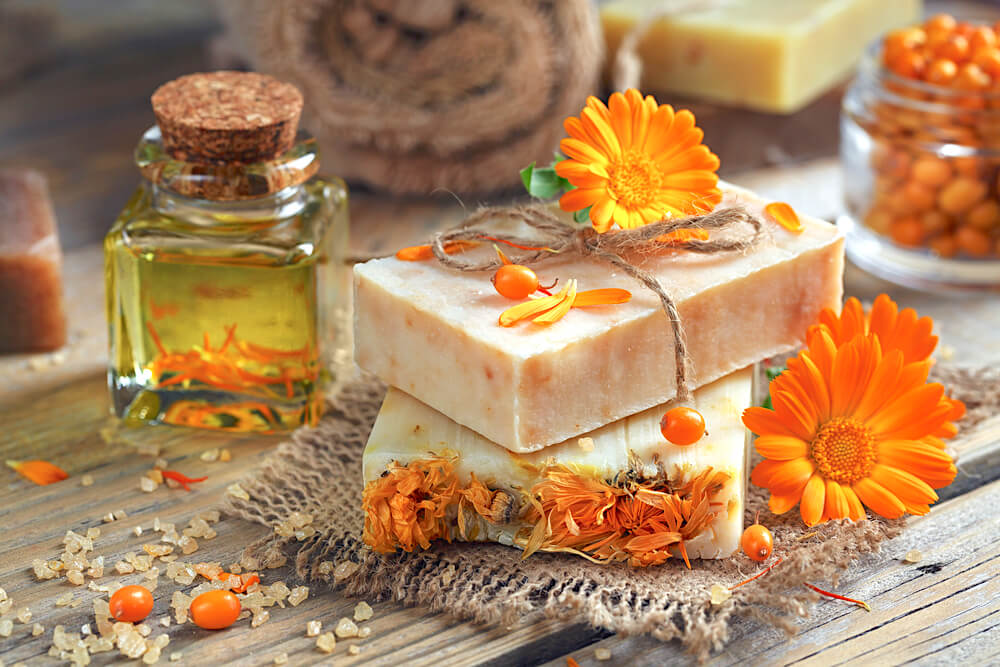 Natural soap on table surrounded by flower petals