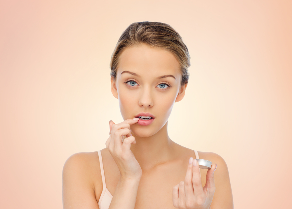 Woman applying lip balm