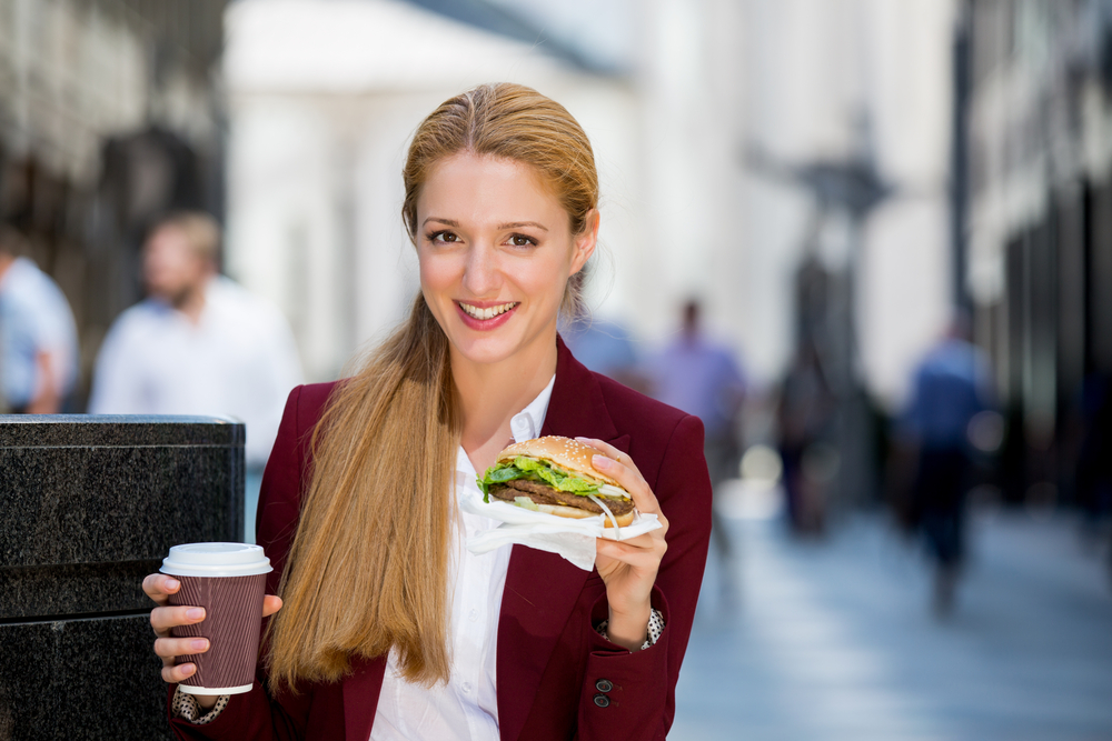 Woman having sandwich outdoors