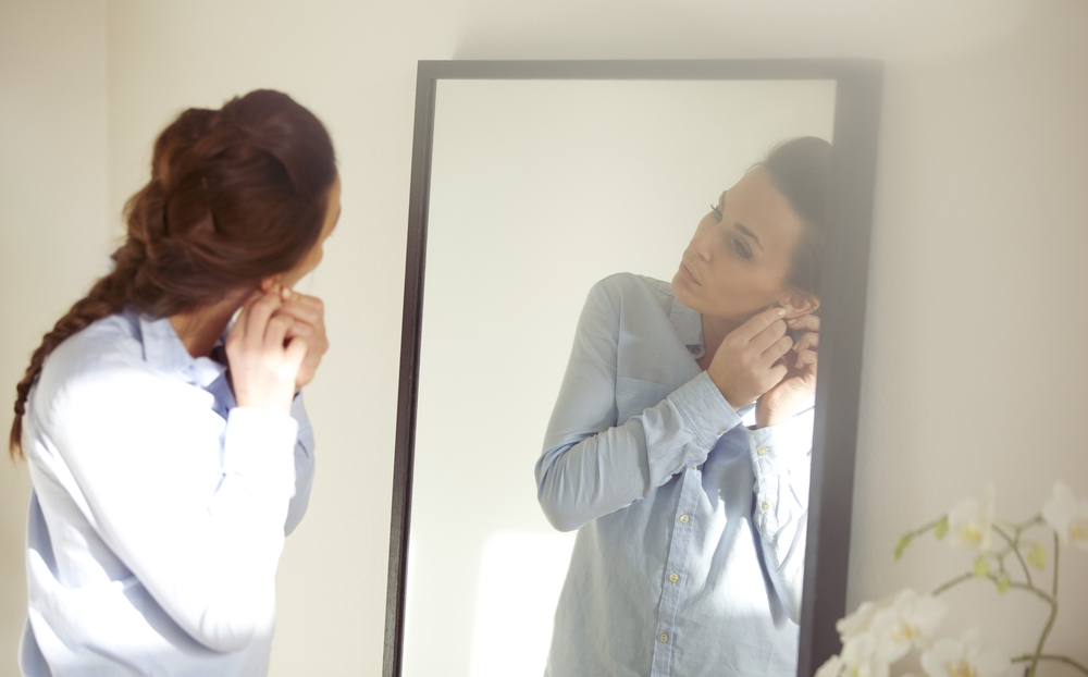 Woman putting on earrings in body-length mirror