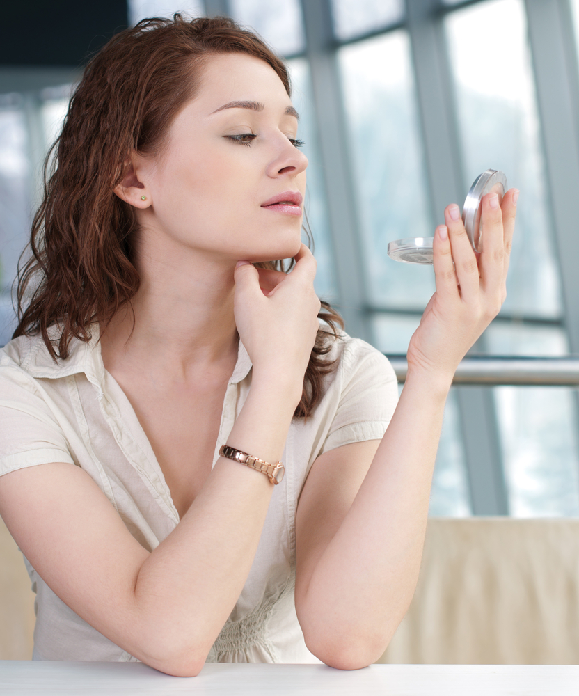 Woman checking her face in compact mirror