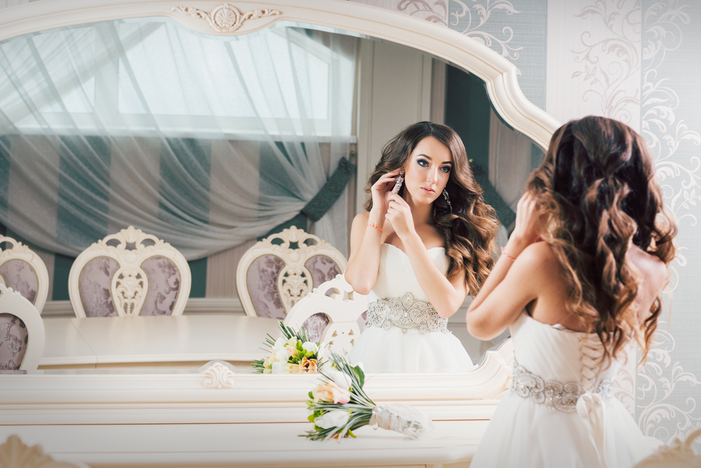 Beautiful bride getting ready in mirror
