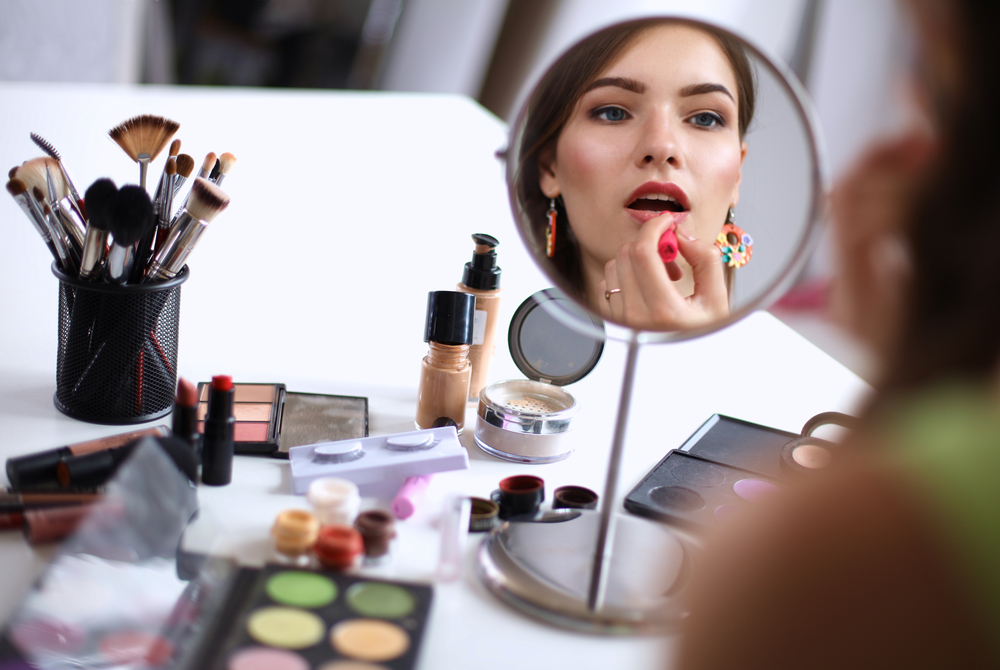 Women applying her makeup at her makeup table.