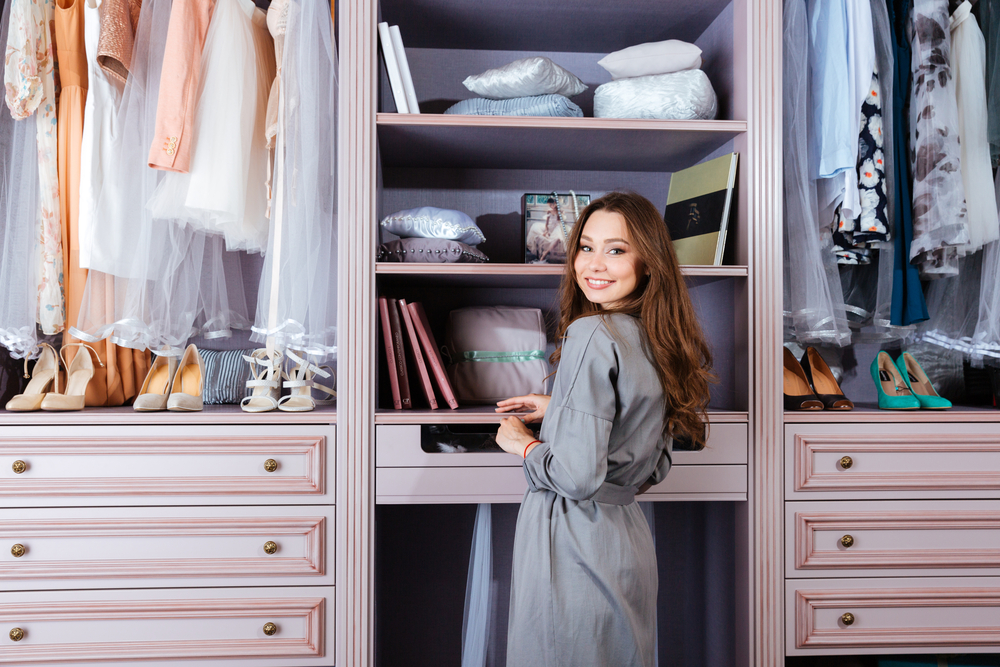 Women standing by her closet looking through clothes.