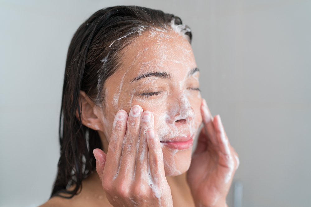 Woman exfoliating face with cleansing product