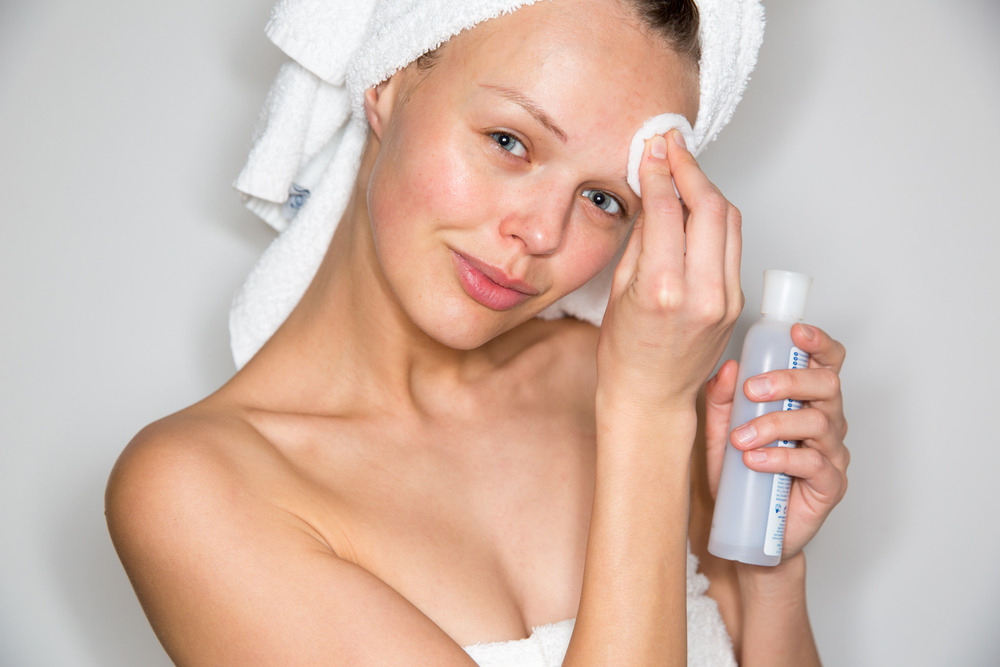 Woman exfoliating skin with cotton pad
