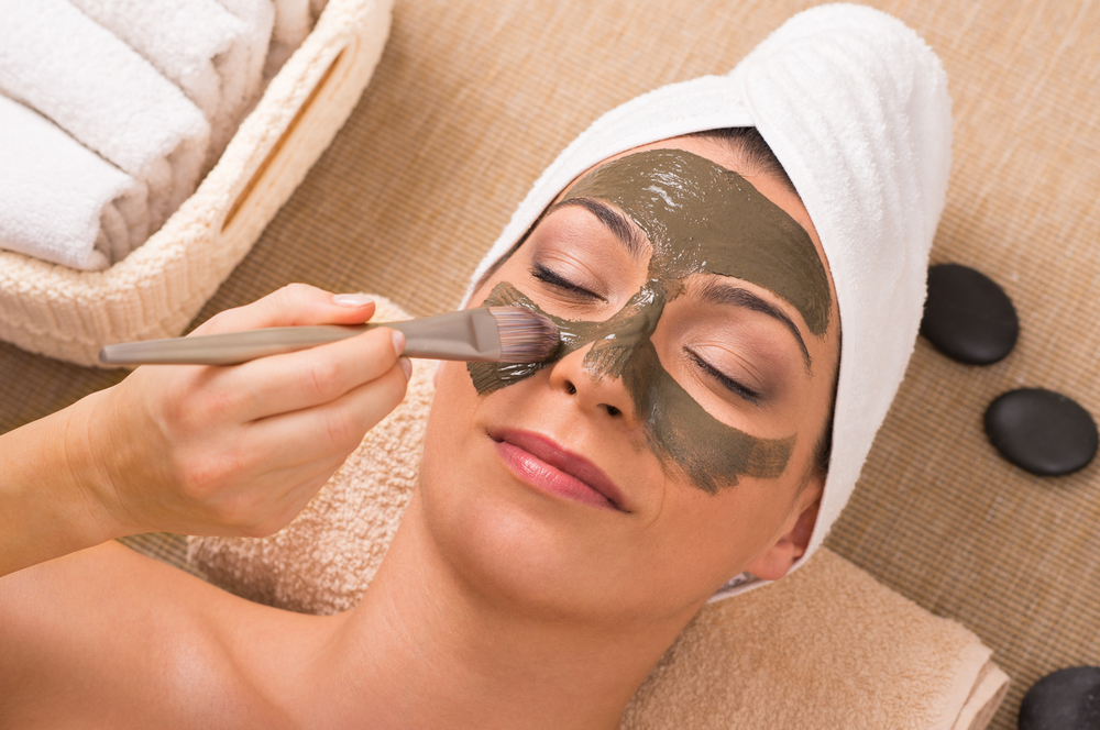 Woman applying exfoliating face mask