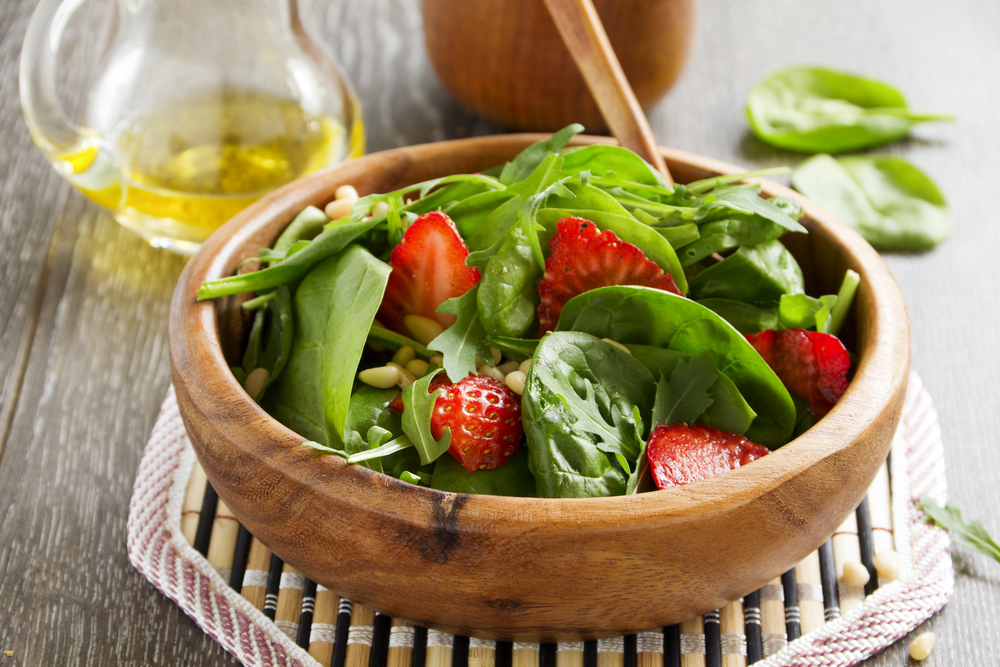 Spinach salad in wooden bowl