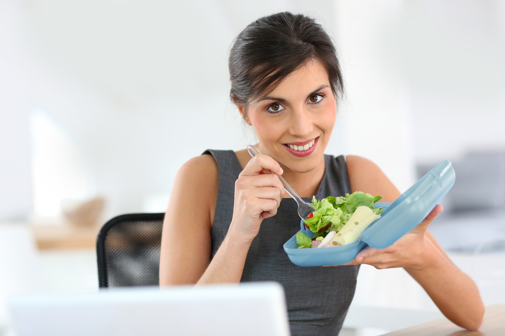Woman eating salad from blue Tupperware