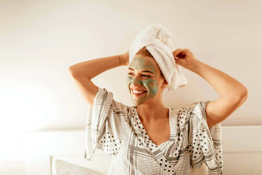 Smiling woman with green face mask and a towel over her hair