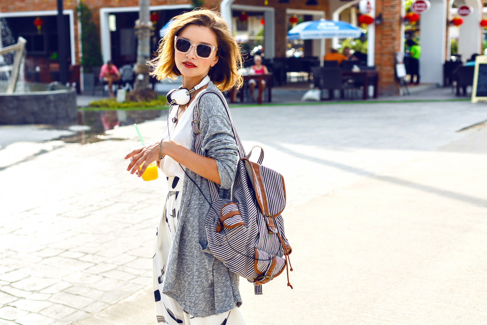 Woman with sunglasses and backpack outdoors