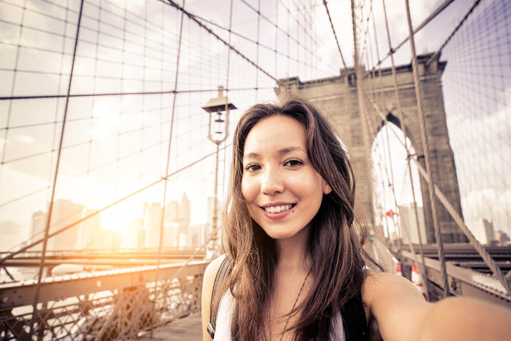 Woman taking a selfie on a bridge