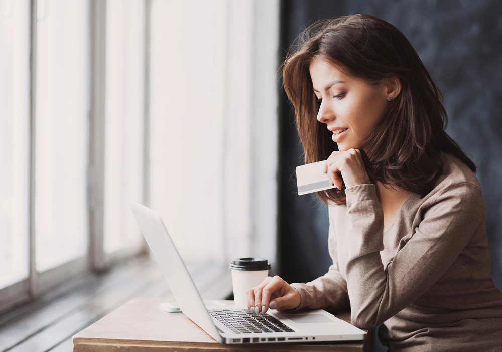 Woman shopping online, holding credit card