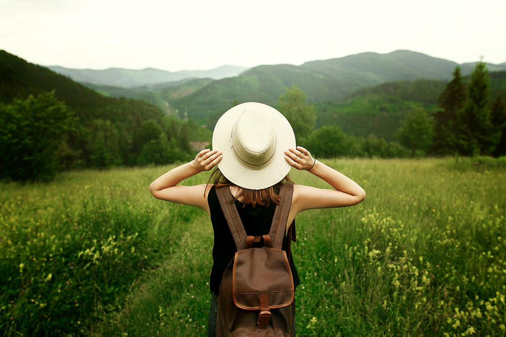 Female traveler surrounded by green fields and mountains