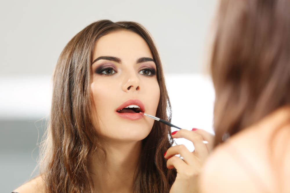 Woman using lip gloss