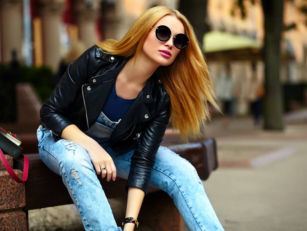 Woman with sunglasses and leather jacket in the city