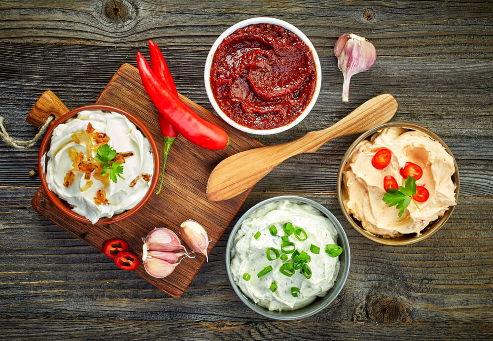Assorted snack dips on wooden table