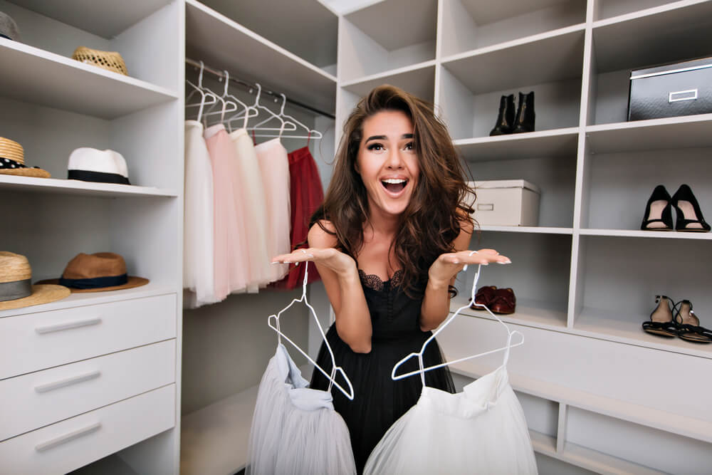 Happy woman holding two dresses in her big closet