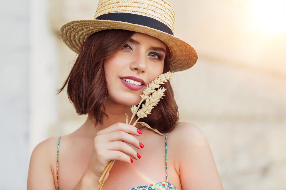 Smiling woman with straw hat and wheat