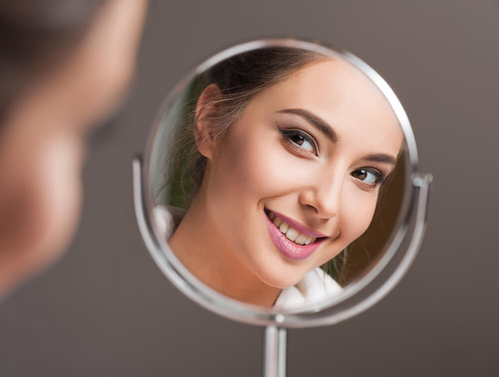 Face of smiling woman reflected in mirror