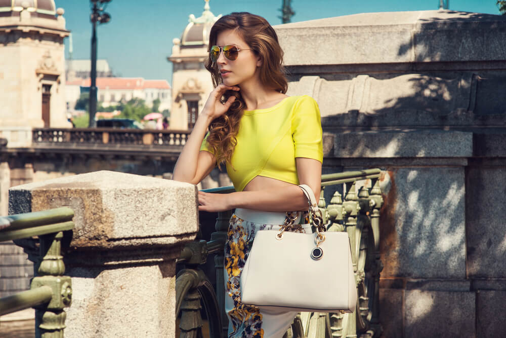 woman with white purse leaning against railing