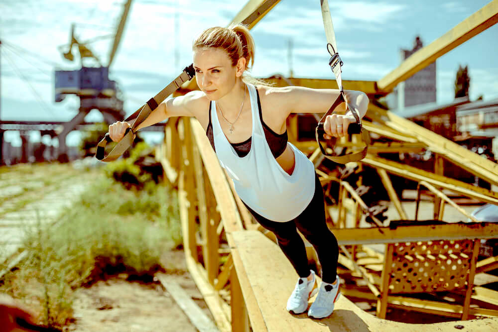 Woman doing TRX exercise on a bridgeq