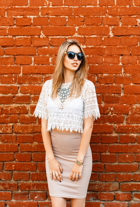 woman in white blouse with statement necklace against red brick wall