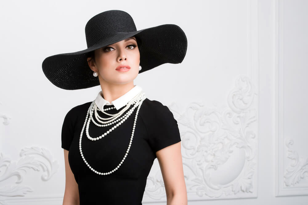 Woman with black hat and pearls