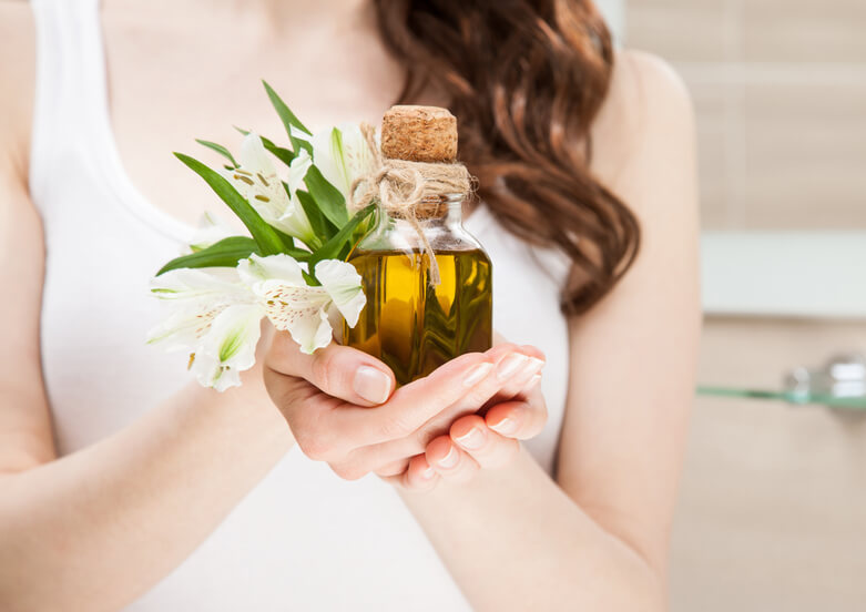 Woman holding botanical oil for hair