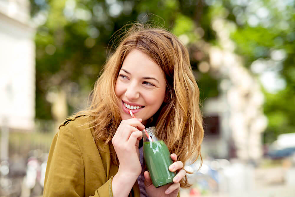 Woman drinking green juice outdoors