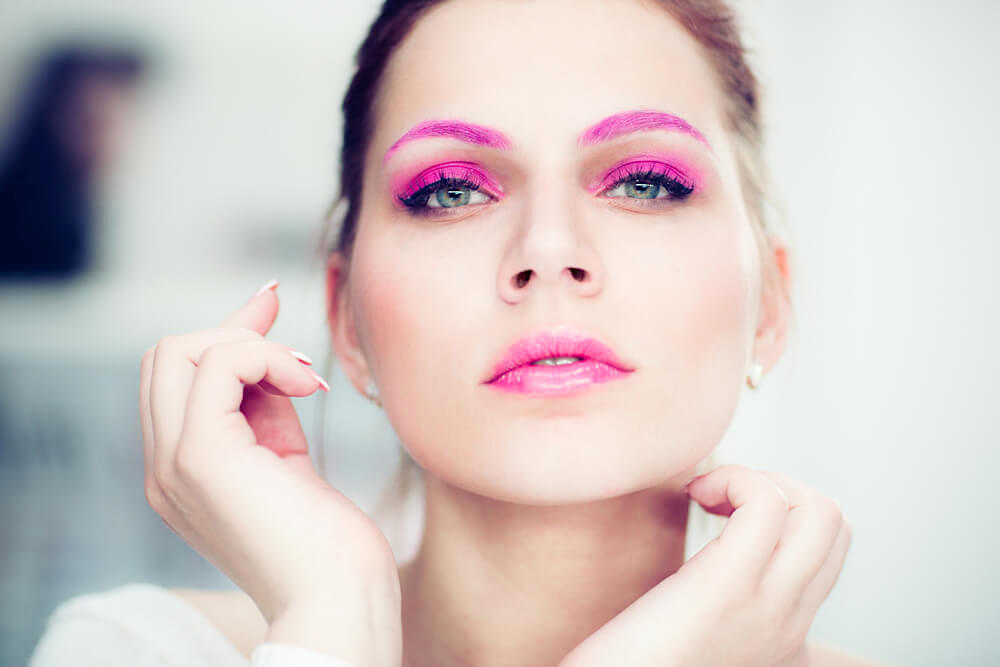 Young woman with bright pink eyeshadow and eyebrows