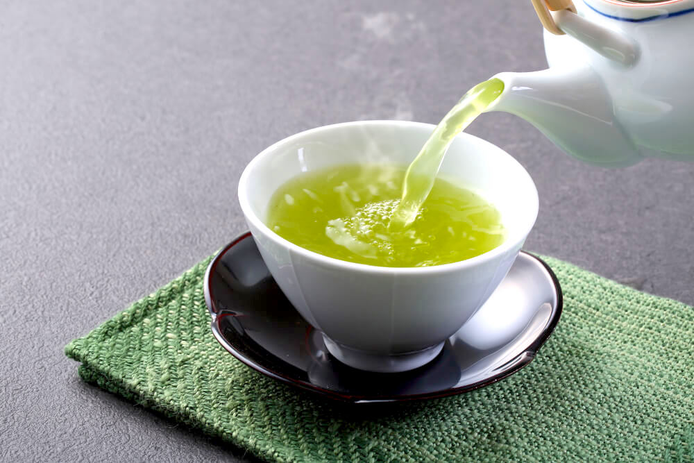 Pouring green tea into small cup