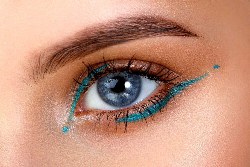 Closeup of woman's eye with blue eyeliner