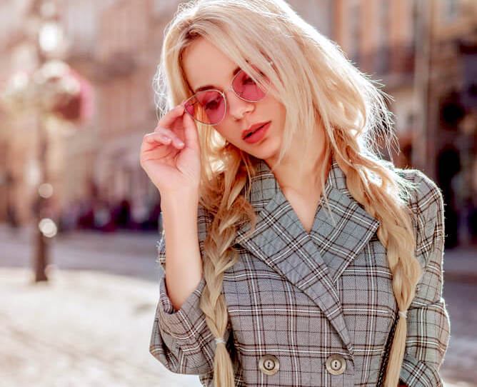 Young blonde woman with rose-tinted sunglasses and loose pigtail braids