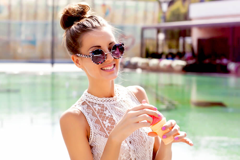 Smiling woman with sunglasses and a high bun by the pool