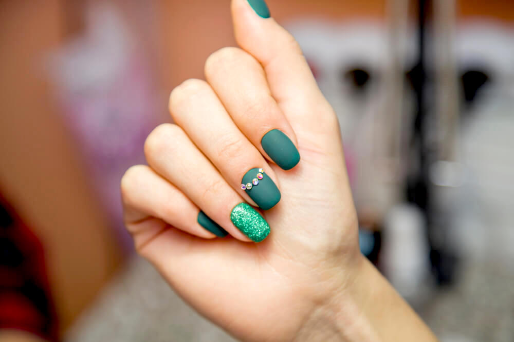 Green manicure with glitter and rhinestones